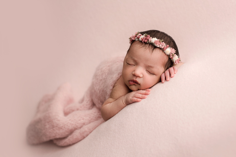 Newborn Girl with Floral Headband on Pink Background